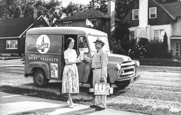 Photo of milkman delivering milk to housewife.