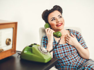 Woman talking on rotary dial phone
